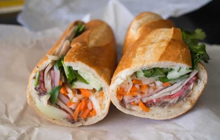 Bahn mi sandwich with carrots, pickled onions, and meat on ciabatta bread