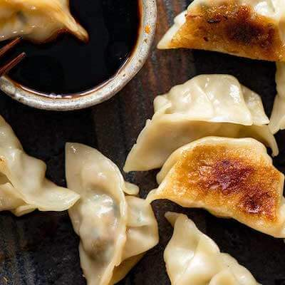 Fried dumplings next to a small bowl of soy sauce