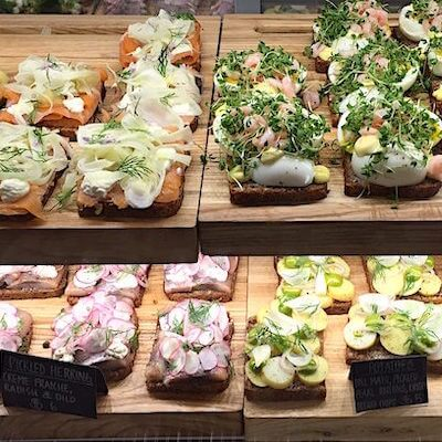 Different kinds of open faced sandwiches with toppings such as smoked salmon and radish