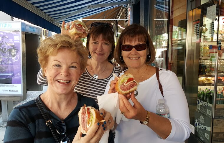 Three women holding large sandwiches filled with meat and vegetables
